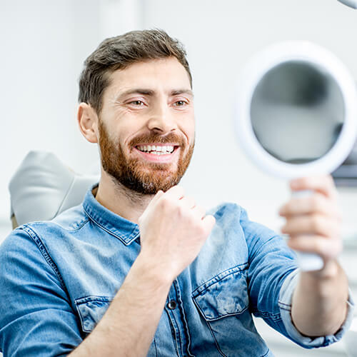 A young bearded men looking at a handheld mirror and smiling