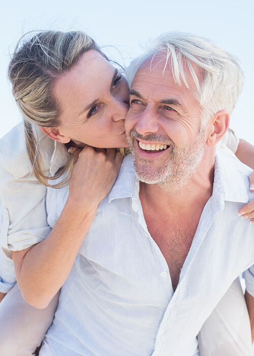 Image of a mature couple outdoors being tender