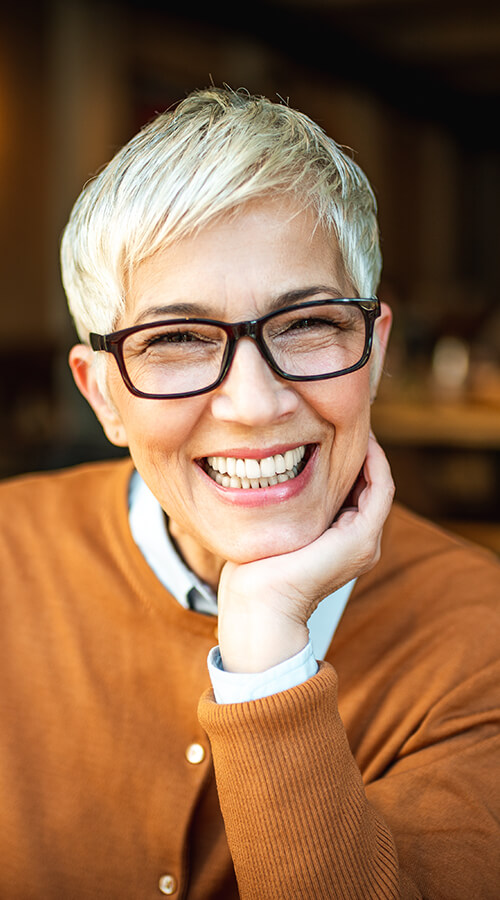 Image of a mature woman with short hair and glasses smiling