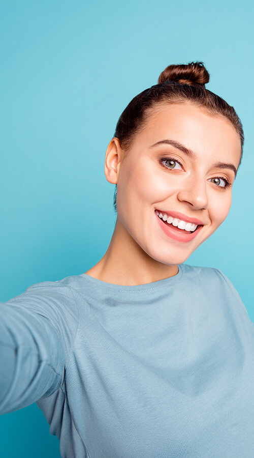 Young woman on a blue background smiling